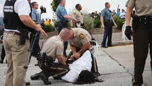 شرطيان يعتقلان أحد المتظاهرين في فيرغسون سبتمبر/ أيلول 2014 خلال مظاهرة كانت تهدف إلى إغلاق طريق عام