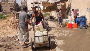 سوريون يملأون حاويات مياه في منطقة تسيطر عليها المعارضة بمخيم اليرموك على المشارف الجنوبية لدمشق