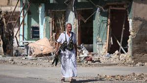 """مقاتل عراقي سني يحمل سلاحه بعد قتال قوات الأمن الحكومية والميليشيات مع جماعة """"الدولة الاسلامية"""" في الضلوعية"""