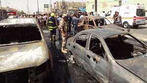 رجال أمن ومواطنون يتجمعون في موقع انفجار سيارة مفخخة وسط سوق تجاري بمدينة كركوك شمال العراق 19 سبتمبر أيلول 2014