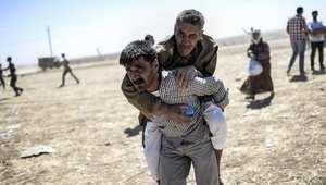 """شاب يحمل عجوزا كرديا، خلال فرارهم من سوريا عبر الحدود إلى تركيا بعد تعرض مناطقهم للقتال من قبل تنظيم """"داعش"""" 20 سبتمبر/ أيلول 2014"""