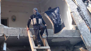 """أحد مقاتلي جبهة النصرة """"القاعدة في بلاد الشام"""" يهبط من أحد المباني المدمرة باستخدام سلم خشبي"""