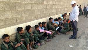 طلاب يمنيون يجلسون خارج مدرستهم في شمال صنعاء بسبب استخدامها لتخزين الأسلحة من قبل الحوثيين