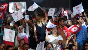 """ناس يلوحون بأعلام تونس وأعلام حزب """"نداء تونس"""" خلال اجتماع الحملة قبل الانتخابات البرلمانية"""