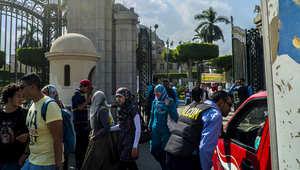 رجل أمن من شركة خاصة يوقف سيارة على أبواب جامعة القاهرة في العاصمة المصرية