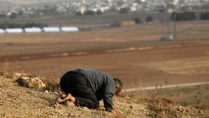 رجل تركي يصلي على الحدود التركية السورية ومدينة كوباني تظهر في الخلفية