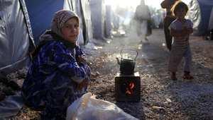 إمرأة كردية من مدينة كوباني السورية تعد الشاي أمام خيمة عائلتها في مخيم للاجئين بتركيا
