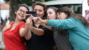 فتيات من تونس يلتقطن صوراً لأصابعهن الملطخة بالحبر بعد التصويت في أول انتخابات برلمانية بعد الثورة