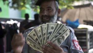 موظف فلسطيني من حماس يعرض أموالا نقدية بعد تلقي جزء من أجره الذي تأخر لعدة أشهر