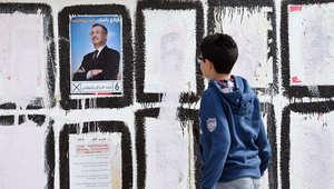 صبي تونسي ينظر الى أحد الملصقات الانتخابية