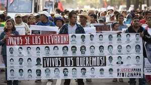 عائلات الطلبة المختفين يرفعون لافتة تحمل صورهم خلال تطاهرة في مكسيكو سيتي 5 نوفمبر/ تشرين الثاني 2014