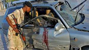 أرشيف - رجل أمن صومالي يتفقد سيارة لمهندس يعمل مع شركة تركية تعرضت لهجوم في مقديشو 27 نوفمبر/ تشرين الثاني 2014