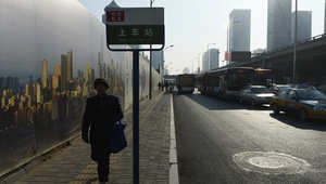 امرأة تمشي على الرصيف في المنطقة التجارية المركزية في بكين