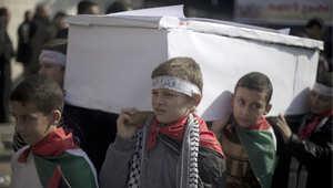 أطفال فلسطينيون يحملون نعشا في مظاهرة بغزة للمطالبة برفع الحصار عن مخيم اليرموك 4 يناير/ كانون الثاني 2014