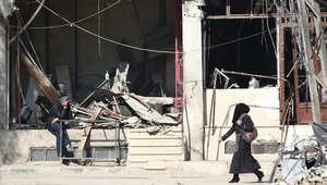 امرأة تسير في أحد شوارع بلدة تحت سيطرة المتمردين في ضواحي دمشق