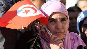 تونسية ترفع علم بلادها وغصن زيتون في ذكرى الثورة التونسية
