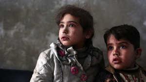 طفلة سورية وشقيقها ينتظران تلقي العلاج في عيادة بمدينة دوما 21 ديسمبر/ كانون الأول 2014
