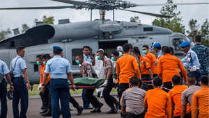 عناصر من البحرية الأمريكية والاندونيسية يخرجون جثث من طائرة مروحية بعد انتشالها من موقع تحطم طائرة خطوط آسيا