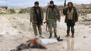 مقاتلون من المعارضة ينظرون إلى جثة أحد المقاتلين الموالين للحكومة في بلدة البريج شمال غرب حلب، 7 يناير/ كانون الثاني 2015