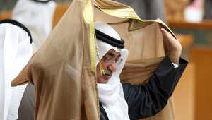 وزير التجارة الكويتي عبد المحسن المدعج يضع عباءته في جلسة للبرلمان في مدينة الكويت