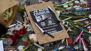 فرنسيون يضعون الزهور والشموع والأقلام مع صور ضحايا هجوم باريس أمام مبنى صحيفة تشاريلي ايبدو 8 يناير/ كانون الثاني 2014
