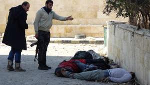 """مقاتلون من الثوار السوريين يقفون إلى جانب جثث أشخاص أعدمهم """"داعش"""" بالقرب من مقر قيادة التنظيم في حلب 28 يناير/ كانون الثاني 2014"""