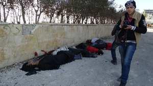 شاب يمر بجانب مجموعة من جثث أشخاص أعدموا على يد داعش في حلب 8 يناير/ كانون الثاني 2014