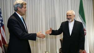 كيري يمد يده لمصافحة ظريف في جنيف خلال جولة المفاوضات التي عقدت في 14 يناير/ كانون الثاني 2015