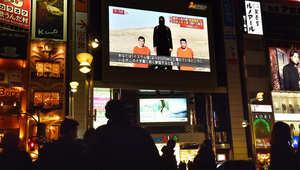 """أشخاص يشاهدون التلفاز عند عرض تقرير اخباري حول الرهينتين اليابانيتين المحتجزين لدى """"داعش""""، طوكيو 20 يناير/ كانون الأول 2015"""