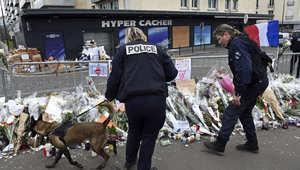 أرشيف - الشرطة مع كلاب بوليسية أمام سوق كوشير الذي احتجز فيه أميدي كوليبالي الرهائن وقتل 4 منهم قبل أن تقتله الشرطة 21 يناير/ كانون الثاني 2015