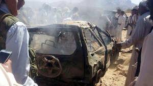 يمنيون يتجمعون حول سيارة محترقة استهدفتها طائرة بدون طيار  يعتقد أنه قتل فيها 3 يشتبه بانتمائهم لتنظيم القاعدة، مأرب - اليمن 26 يناير/ كانون الثاني 20015