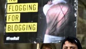 """ناشطون من منظمة العفو الدولية في احتاج بالعاصمة الألمانية بريلين، على جلد المدون السعودي رائف بدوين يرفعون شعار """"لا جلد بسبب التدوين"""" 29 يناير/ كانون الثاني 2015"""
