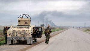 مقاتل من البيشمرغة على إحدى الطرق في كركوك فيما يبدو الدخان في الأفق حيث شن تنظيم داعش هجوما على المدينة 30 يناير/ كانون الثاني 2015