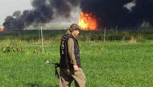 أحد مقاتلي البيشمرغة الكردية في حقل خباز النفطي، 25 كيلومتر غرب كركوك، ويظهر تصاعد الدخان من الحقل الذي استعادت السيطرة عليه من داعش، 2 فبراير/ شباط 2015