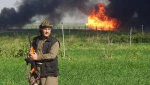 مقاتل كردي تظهر خلفه سحابة من الدخان تنبعث من حقل خباز غرب كركوك بعد استعادة البيشمرغة السيطرة عليه من تنظيم داعش، 2 فبراير/ شباط 2015
