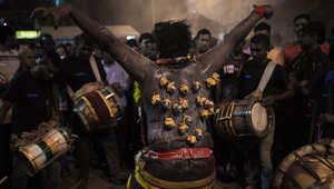 يرقص بطريقه للمعبد حاملا القرابين بخطاطيف مغروسة بظهره