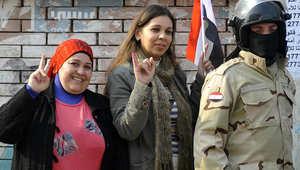 نساء مصريات بجانب عضو من قوات الأمن بعد الادلاء بأصواتهم على الدستور الجديد في يناير 2014