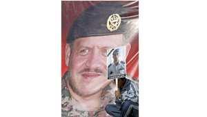 """طالب يحمل صورة للطيار الأردني معاذ الكساسبة الذي أعدمه """"داعش"""" ويجلس إلى جانب صورة ضخمة للملك عبدالله الثاني خلال مسيرة في عمان، 5 فبراير/ شباط 2015"""