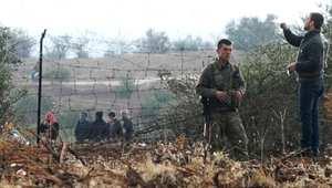 جنود أتراك يرقبون لاجئيين سوريين وهم يعبرون السياج الحدودي، هربا من القتال الدائر في سوريا، 15 يناير/ كانون الثاني 2014