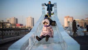 أطفال يلهون على مزلاج من الثلج في أولان باتور عاصمة منغوليا