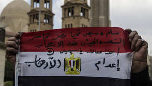 مصري يحمل علما كُتب عليه عبارات داعمة الرئيس عبدالفتاح السيسي والوحدة الوطنية ومكافحة الإرها