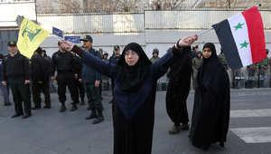 متظاهرة ايرانية تحمل علم حزب الله والعلم السوري خلال مظاهرة بالقرب من السفارة السويسرية في طهران