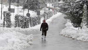 رجل يسير في شارع تغطيه الثلوج بعد عاصفة ثلجية ضربت العاصمة الأردنية عمان