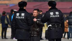 الشرطة الصينية تسجوب أحد الأشخاص في ساحة تيانانمين أمام مجلس الشعب في بيكن، 2 مارس/ آذار 2015
