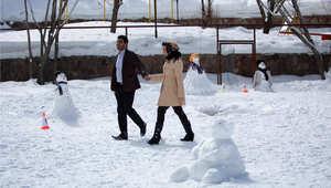 زوجان يمشيان بين مجموعة من التشكيلات الثلجية