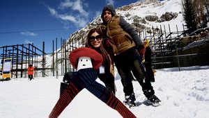 """عائلة إيرانية تقف قرب """"امرأة الثلج"""" قاموا بتشكيلها خلال المسابقة."""
