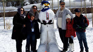 عائلة تلتقط صورة جماعية مع رجل الثلج الذي صنعته