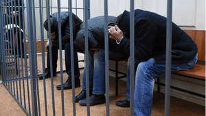 ثلاثة أشخاص غير محددي الهوية معتقلين بتهمة مقتل نيمستوف يغطون وجوههم داخل القفص في محكمة مقاطعة بسماني الروسية، 8 مارس/ آذار 2015