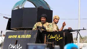 """مقاتلون شيعة من """"سرايا السلام"""" التابعة لمقتدى الصدر، والتي تقاتل إلى جانب الحكومة العراقية ضد تنظيم داعش، يغادرون بغداد باتجاه سامراء 15 مارس/ آذار 2014"""
