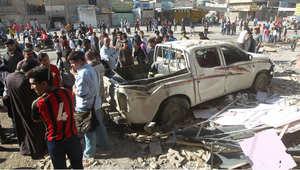 عراقيون يقفون في موقع تفجير سيارة بمدينة الصدر ببغداد، 23 مارس/ آذار 2015